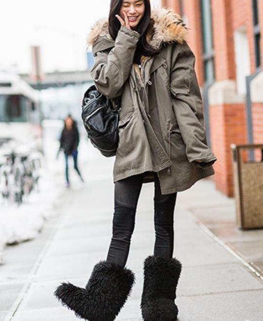 Κοπέλα φοράει μαύρα γυναικεία μποτάκια με γούνα από τα Olympic Stores.